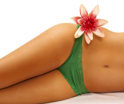 Intimate part of a woman's body in green panties and flower on her hip.